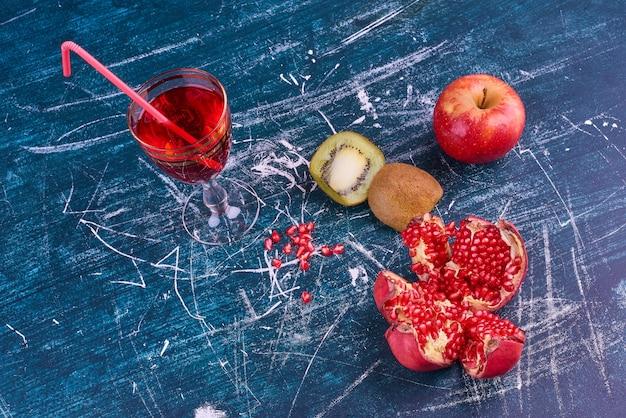 Frutta mista e un bicchiere di succo, vista dall'alto.