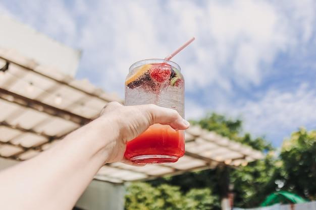 Mixed fruits pink italian soda against sunny sky of summer
