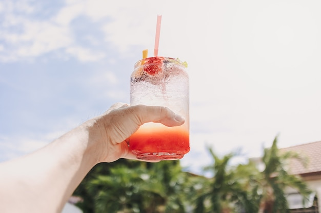夏の晴れた空を背景にミックスフルーツピンクソーダ