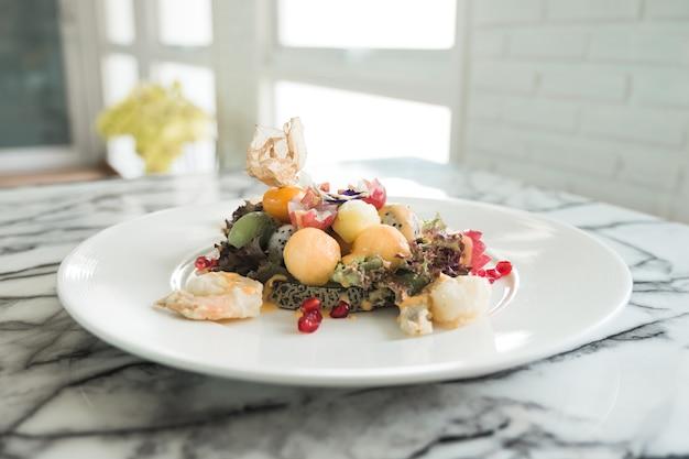 Салат из смешанных фруктов с обжаренными креветками на белой тарелке в ресторане