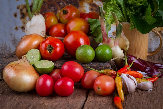 Mixed fruits and vegetables on old wood table background