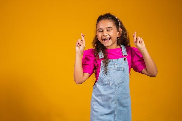 노란색 배경에 고립되어 자신의 소원이 이루어지기를 바라는 혼합된 재미있는 어린 소녀가 손가락을 교차합니다. 행운이나 기적을 기원하며 기도하는 어린 소녀의 초상화