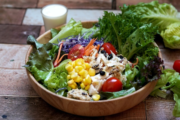 Mixed greens salad and boiled chicken in a wooden bowl