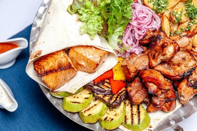 혼합 그릴 고기 튀김 야채와 구운 연어 생선 필레 장식 따뜻한 요리