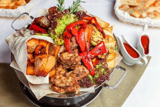 Mixed grill meat, fried vegetables and grilled salmon fish fillets decoration in warm dish