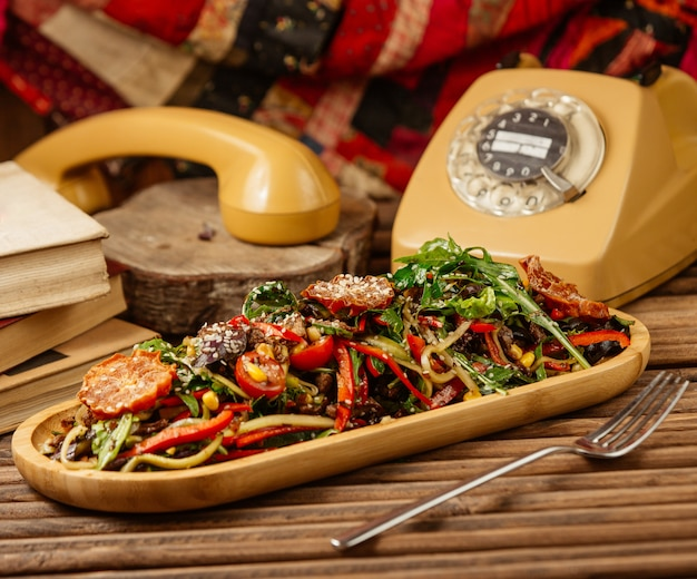 Mixed grilled vegetable salad with herbs and olive oil in wooden plate with a vintage telephone around.