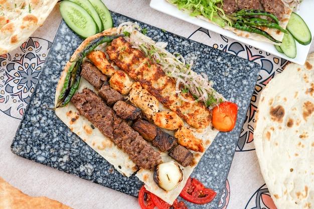 Mixed grills, kebab, tikka on bread on a cutting board