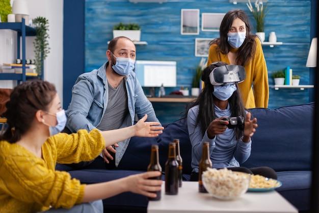 Смешанная группа людей ведет чернокожую женщину с гарнитурой vr, играющую в виртуальные видеоигры в гостиной, сохраняя социальное дистанцирование от covid19. разнообразные друзья веселятся на новой нормальной вечеринке.