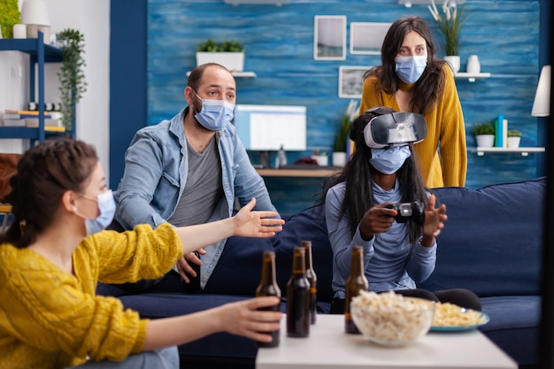 Mixed group of people guiding black woman with vr headset playing virtual video games in living room keeping social distancing agaist covid19. diverse friends having fun at new normal party.