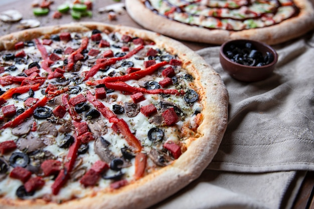 Mixed ingredient pizza with chopped red pepper and black olives