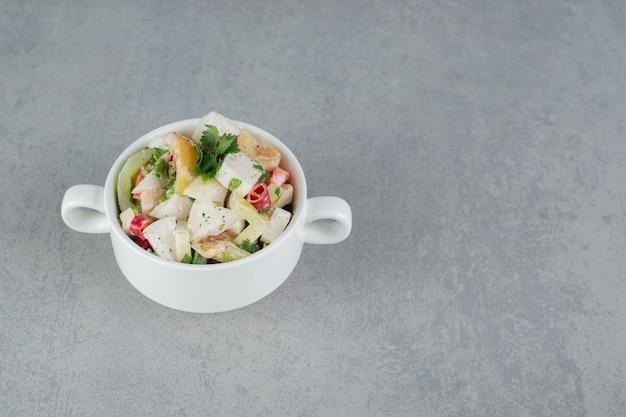 Сезонный салат из смешанных ингредиентов с овощами и фруктами в белом блюде.