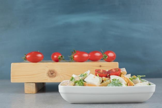Смешанные ингредиенты овощной и фруктовый салат в белой чашке.