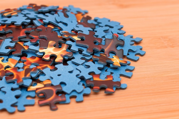Mixed jigsaw puzzle peaces on wooden table