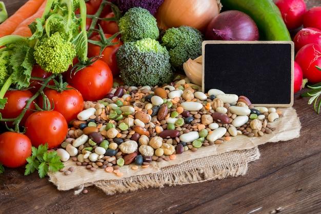 混合豆類と茶色の木製のテーブルに黒板と生野菜をクローズアップ