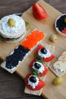 Mixed light cracker sandwiches on a wooden board.