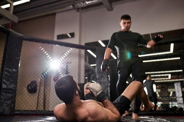 黒服を着た総合格闘家の男が勝ち、ジムでリングで激しく戦った後、負けた戦闘機の上に立ちます。ボクシング、総合格闘技、スポーツのコンセプト。上半身裸の男性の背面図に焦点を当てる