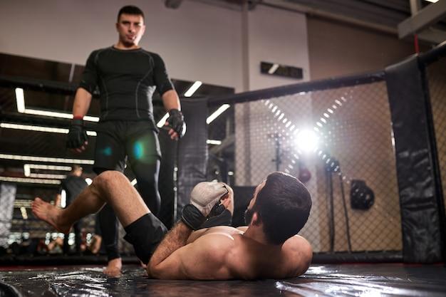黒服を着た総合格闘家の男が勝ち、ジムでリングで激しく戦った後、負けた戦闘機の上に立ちます。ボクシング、総合格闘技、スポーツのコンセプト。上半身裸の男性に焦点を当てる