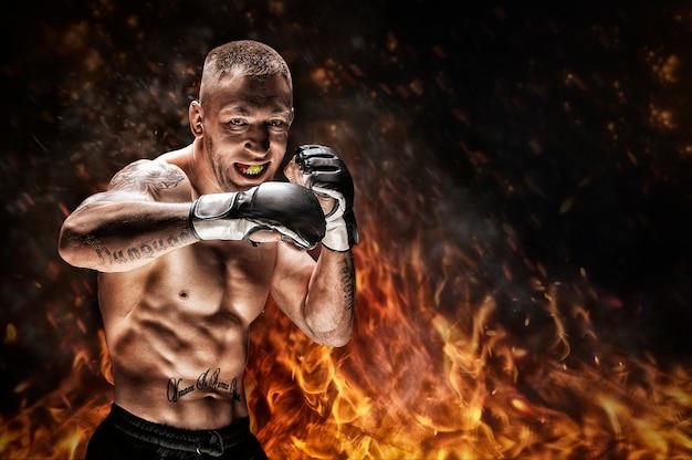 火と煙を背景にポーズをとる総合格闘家。 mma、タイのボクシング、古典的なボクシングの概念。ミクストメディア