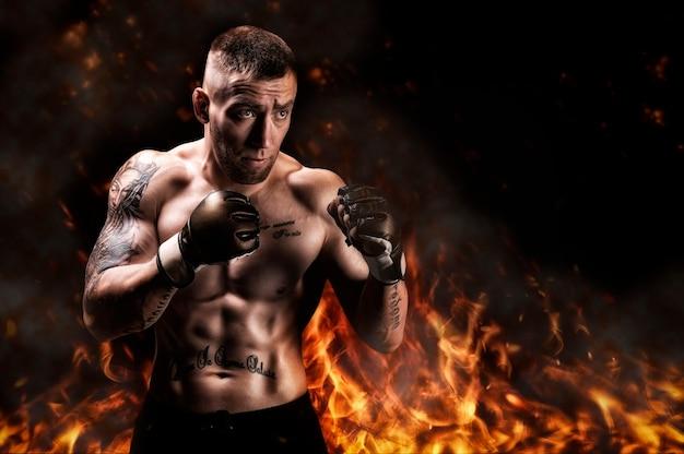火と煙を背景にポーズをとる総合格闘家。 mma、ufc、タイのボクシング、古典的なボクシングの概念。ミクストメディア