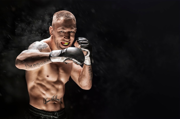 Mixed martial artist posing on a black background. concept of mma, thai boxing, classic boxing. mixed media