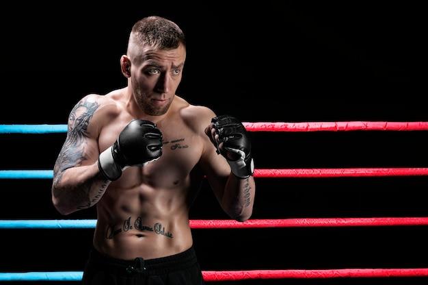 ボクシングのリングでポーズをとる総合格闘家。 mma、ufc、タイのボクシング、古典的なボクシングの概念。ミクストメディア