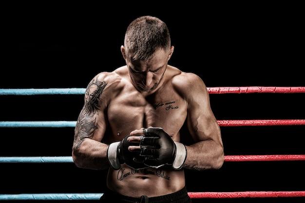 Мастер смешанных единоборств позирует на боксерском ринге. концепции mma, ufc, тайского бокса, классического бокса. смешанная техника