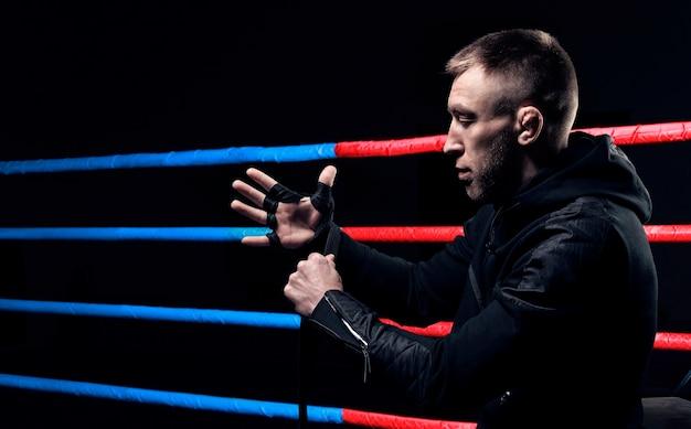 Мастер смешанных единоборств обматывает кулак повязкой. концепции mma, ufc, тайского бокса, классического бокса. смешанная техника