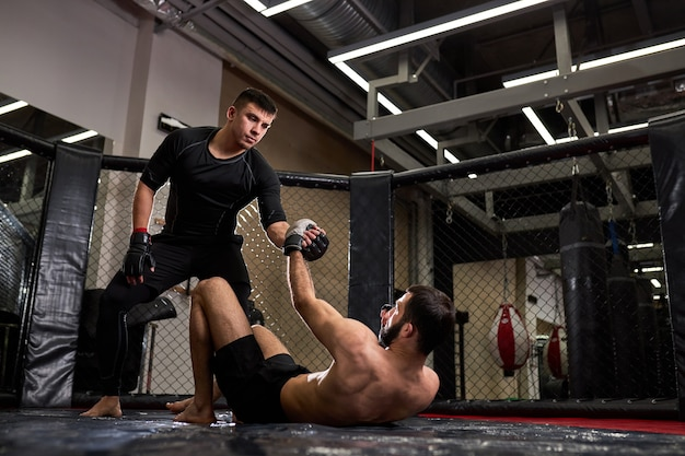 Mixed martial artists during fight, help each other, in ring at gym. man in black wear holds out hand to shirtless male, engaged in kickboxing