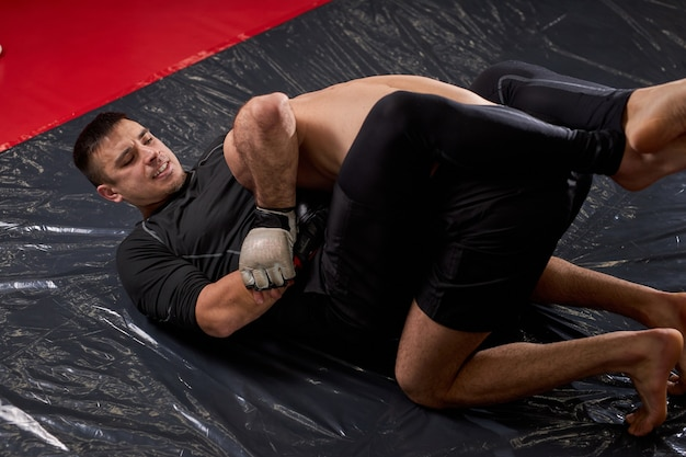 Mixed martial artists fighting on mat using grappling, fight without rules. strong and confident men having no fear, sparring, training exercising