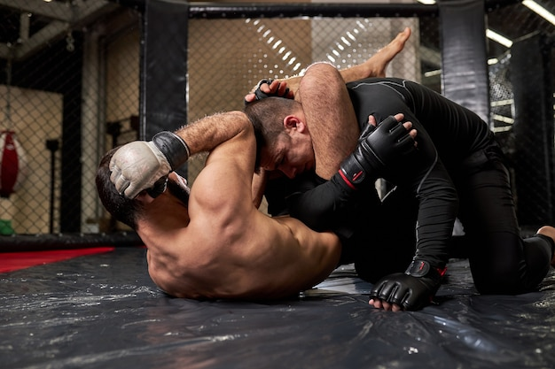Mixed martial artists punching each other, fighting without rules at gym, training. aggressive boxers sparring, having strong powerful muscles, lying on ground floor