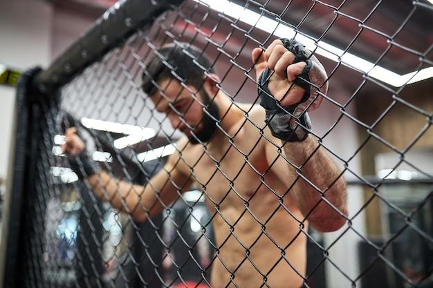 Смешанные боевые искусства. мма, сильный боец в октагоне, отдыхает на ринге после боя, нуждается в отдыхе, мускулистый мужчина без рубашки смотрит вниз. сосредоточиться на руках на перчатках