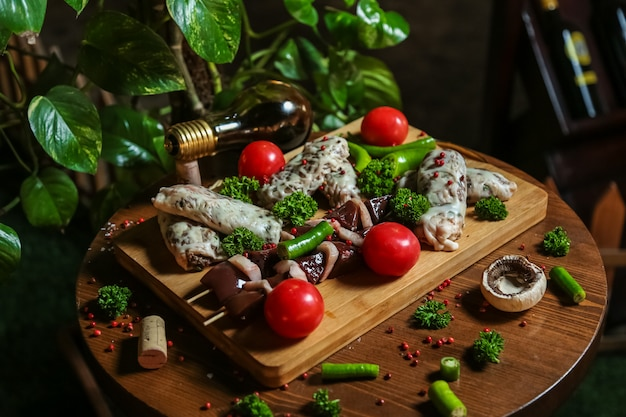 Mixed meat on the wooden board with tomatos, mushrooms and pepper