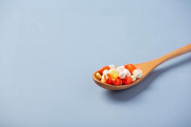 Mixed medicine pills, tablets on wooden spoon
