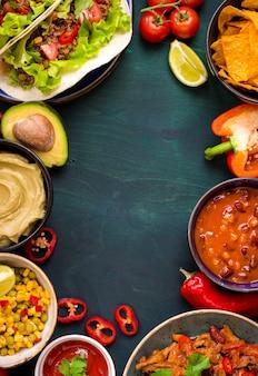 混合メキシコ料理の背景。パーティーフード。ワカモレ、ナチョス、ファヒータ、ミートタコス、サルサ、ピーマン、トマトを木製のテーブルに。テキスト用のスペース。