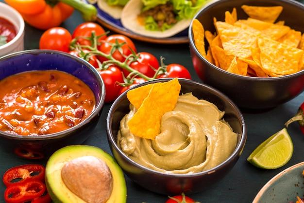 混合メキシコ料理。パーティーフード。ワカモレ、ナチョス、ファヒータ、ミートタコス、サルサ、ピーマン、トマトを木製のテーブルに。上から。