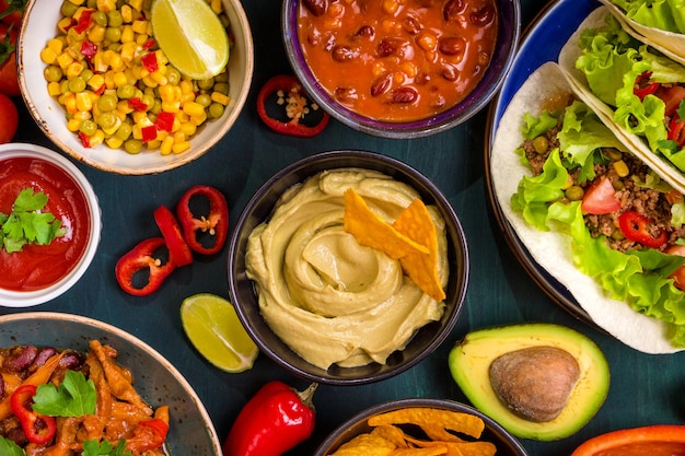 混合メキシコ料理。パーティーフード。ワカモレ、ナチョス、ファヒータ、ミートタコス、サルサ、ピーマン、トマトを木製のテーブルに。上面図。