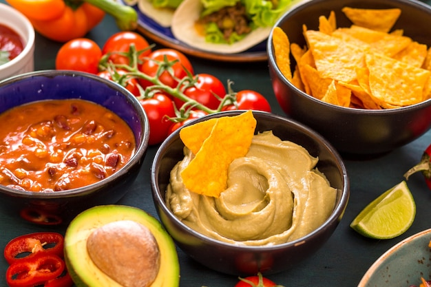 Mixed mexican food. party food. guacamole, nachos, fajita, meat tacos, salsa, peppers, tomatoes on a wooden table. from above.