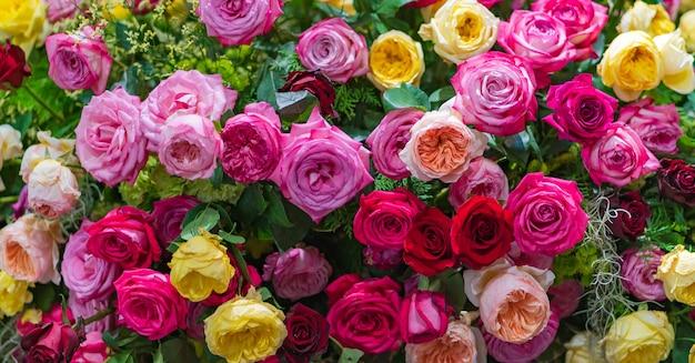 花のインテリアで混在したマルチカラーのバラ、カラフルな結婚式の花の背景