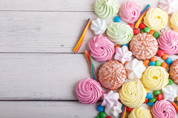 Mixed multicolored candies on white wooden background.