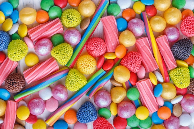 Mixed multicolored candies on white wooden background