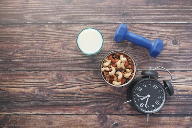 Mixed nut in a bowl milk and dumbbell on table