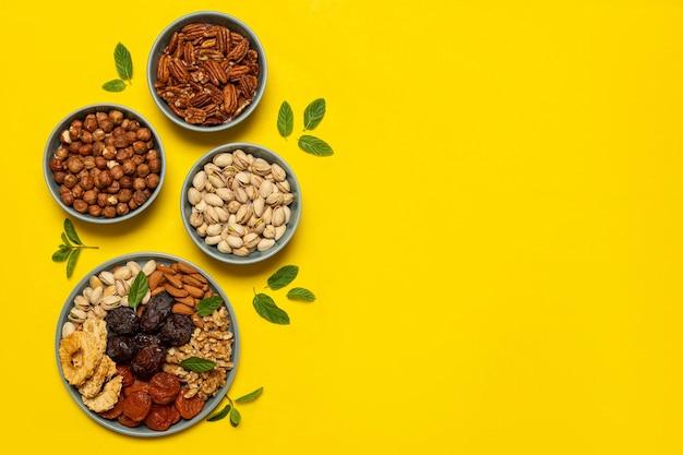 コピースペースのある黄色の背景のプレートにミックスナッツとドライフルーツ。トゥビシュバットのユダヤ教の祝日のシンボルヘルシースナック-オーガニックナッツとドライフルーツのミックス。