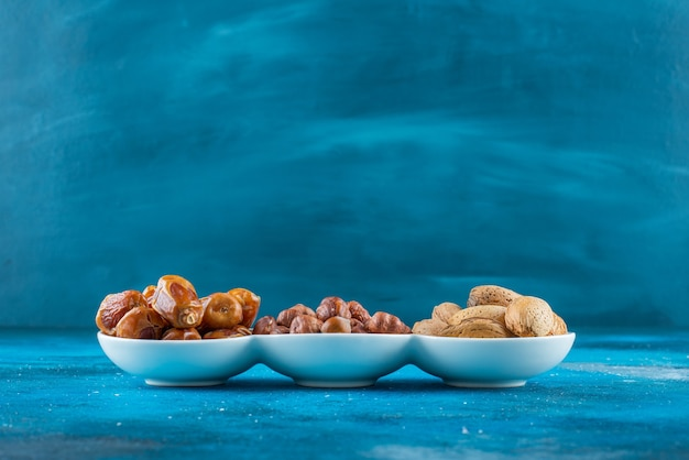 A mixed of nuts in a bowl on the blue surface