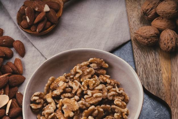 セラミックボウル、木のスプーンのミックスナッツ。アーモンド、クルミ、カシューナッツ、ピスタチオナッツ