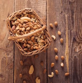 古い木製の背景にミックスナッツ