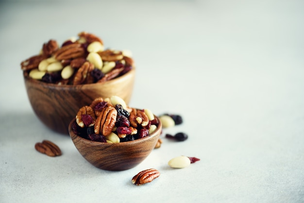 Mixed nuts and raisins in wooden bowl.