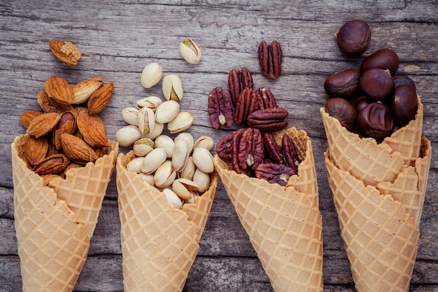 Mixed nuts in waffle cones on shabby wooden background for sweets menu design.