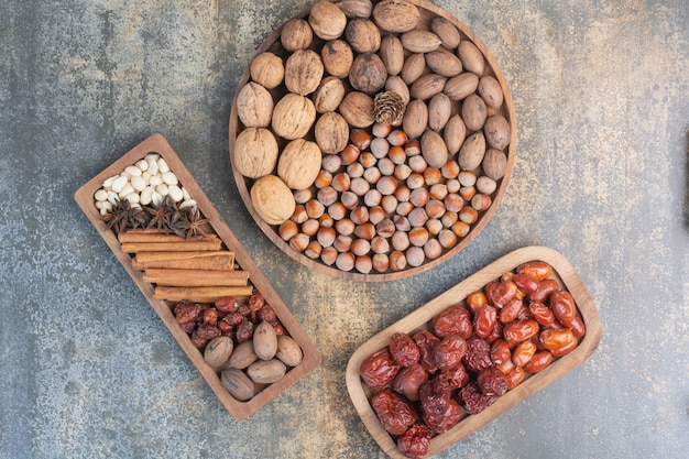 Mixed nuts with cinnamon sticks and dried fruit on wooden plate. high quality photo