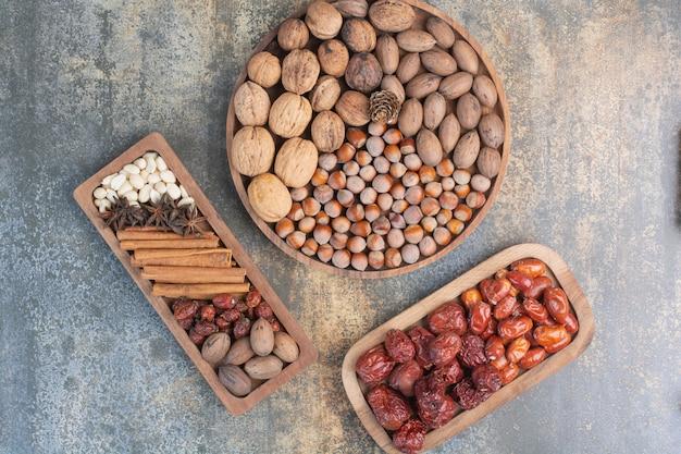 Noci miste con bastoncini di cannella e frutta secca sul piatto di legno. foto di alta qualità