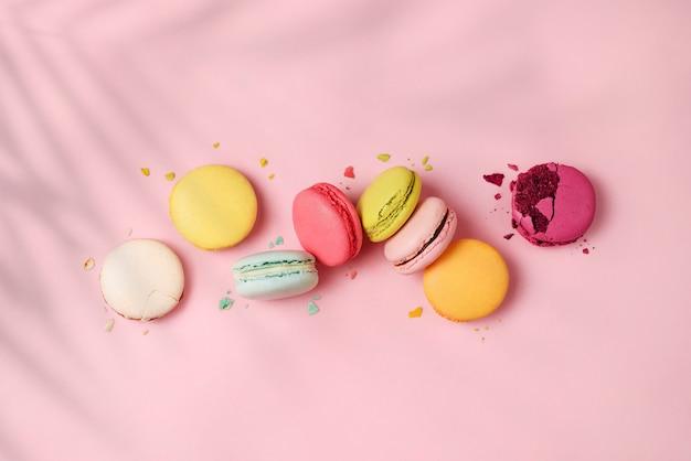 影付きのピンクの背景にカラフルなマカロニまたはパスタケーキのミックス。甘くてカラフルなフレンチマカロン、パステルカラー。フラットレイ、上面図。
